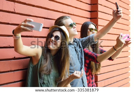 Young people having fun outdoor and making selfie with smart phone against red brick wall. Urban lifestyle, happiness, joy, friends, self photo social network concept. Image toned and noise added.