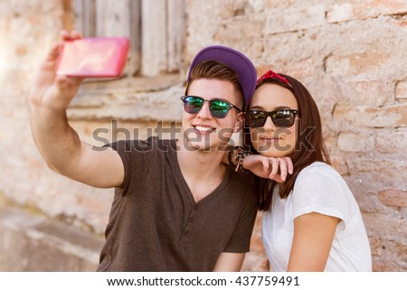 Young people having fun outdoor and making selfie with smart phone against red brick wall. Urban lifestyle, happiness, joy, friends. Instagram - stock photo