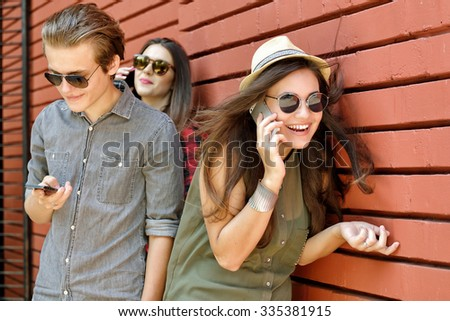 Young people having fun outdoor using gadget Urban lifestyle, internet and gadget dependence, friends, social network concept. Image toned and noise added. - stock photo