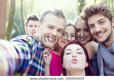 Young people having good time together in park on river and taking selfie - stock photo