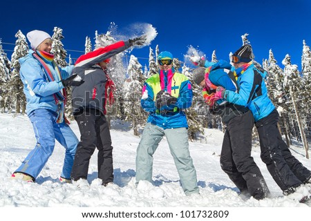 Young people having snowball fight in snow in winter background - stock photo