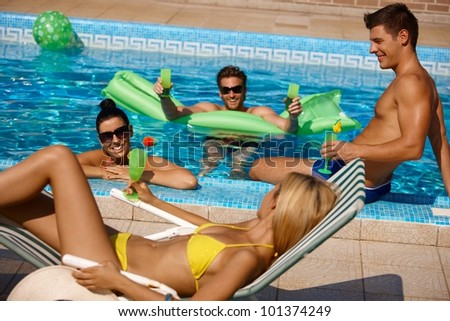 Young people having summer fun in outdoor pool. - stock photo
