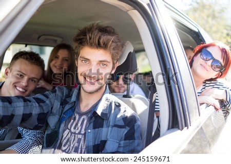 Young people having vacation enjoying fun driving car - stock photo