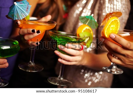 Young people holding cocktails at a birthday party, their faces being offscreen - stock photo