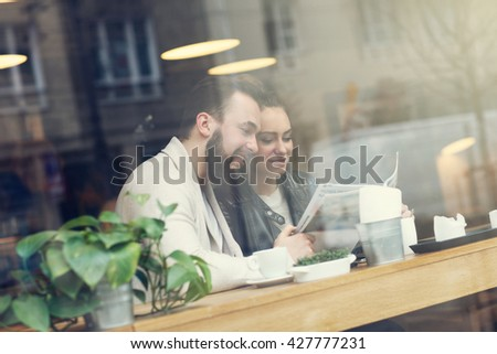 Young people in cafe looking at guide - stock photo