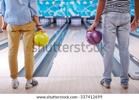 Young people in casualwear standing in bowling alley - stock photo