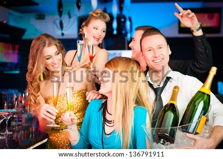 Young people in club or bar drinking champagne and having fun; one man is looking into the camera