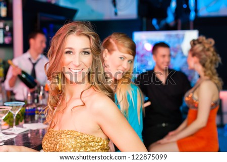Young people in club or bar drinking champagne and having fun; one woman is looking into the camera - stock photo