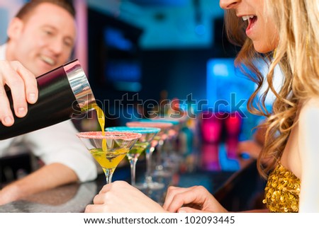 Young people in club or bar drinking cocktails and having fun; the barkeeper is mixing drinks