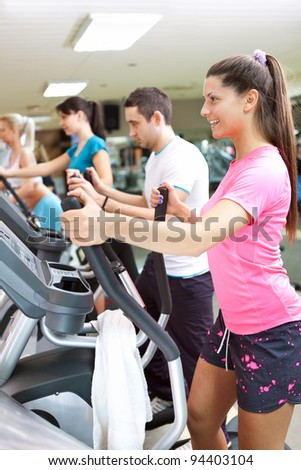young people in gym running on treadmills - stock photo