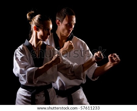 Young people in kimono make martial arts exercise on black - stock photo