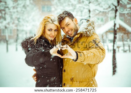 young people in love cuddling and show signs of a heart-shaped finger under the snow. Horizontal color photo - stock photo