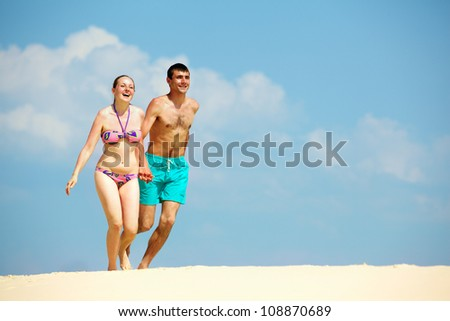 Young people in love walking on the sand holding hands - stock photo