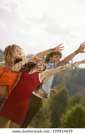 Young people in meadow, arms up - stock photo