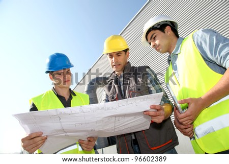 Young people in professional training on industrial site - stock photo