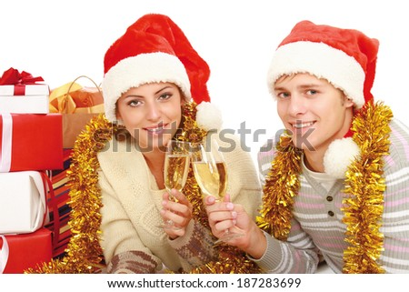 Young people in santa hat drinking champagne isolated on white background - stock photo