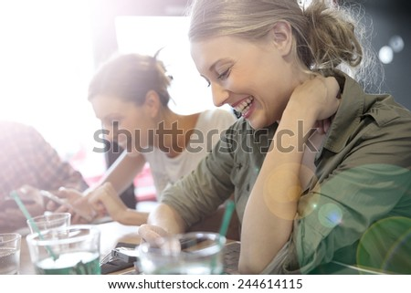 Young people in snack bar, connected on smartphone - stock photo