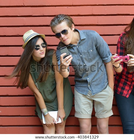 Young people in sun glasses having fun summer outdoor and making selfie with smart phone against red brick wall. Urban lifestyle, happiness, joy, friends, self photo social network concept.  - stock photo
