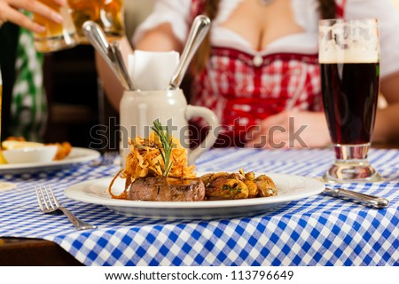 Young people in traditional Bavarian Tracht eating in restaurant or pub lunch or dinner - stock photo