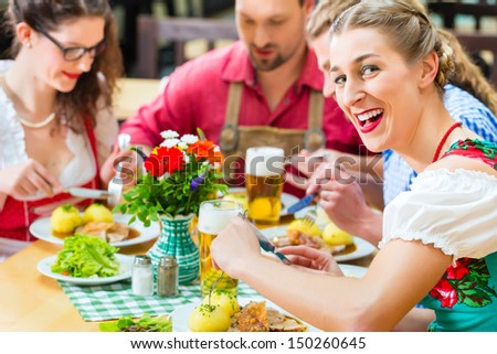 Young people in traditional Bavarian Tracht eating pork in restaurant or pub for lunch or dinner - stock photo