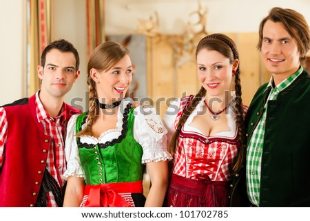 Young people in traditional Bavarian Tracht in restaurant or pub - stock photo