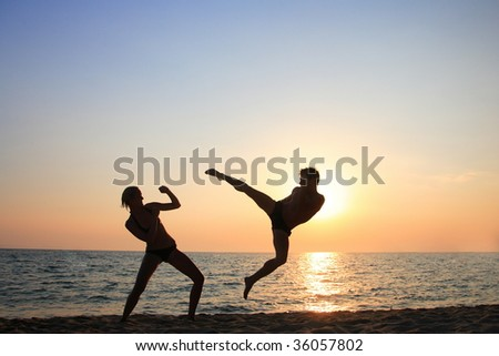 Young people in training at sunset - stock photo