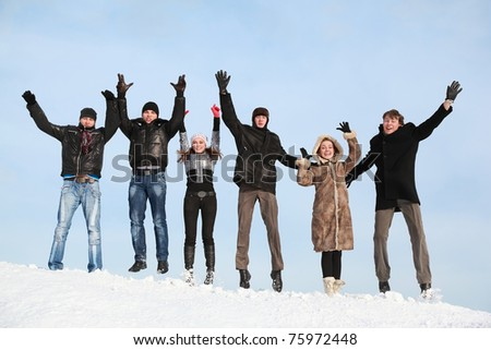 Young people jump in winter on snow and lift hands upwards - stock photo