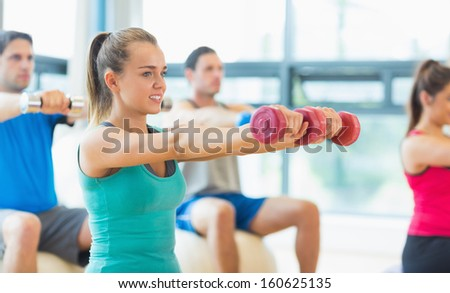 Young people lifting dumbbell weights with trainer in the gym - stock photo