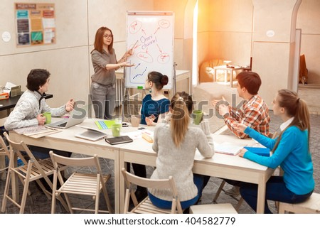 Young People listening Presentation of female Manager active Participants asking Questions in Meeting Room with wood Walls and Table using Flip Chart - stock photo