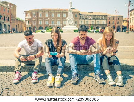 Young people looking down at cellular phone - Teenagers sitting outdoors and texting with their smartphones - Concepts about technology and global communication - stock photo