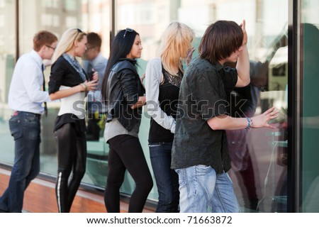 Young people looking through a shop windows - stock photo