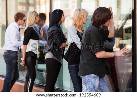 Young people looking through the mall window - stock photo