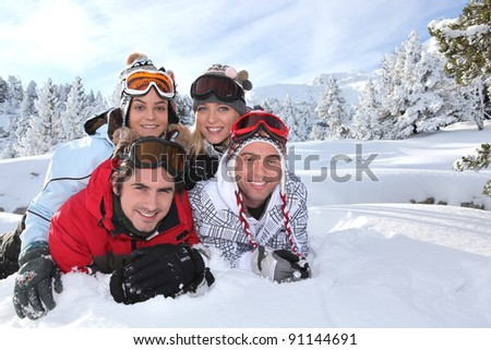 Young people lying in the snow - stock photo