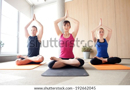 Young people meditating in a yoga class - stock photo