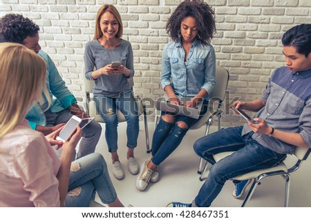 Young people of different nationalities are using gadgets while working in circle. Beautiful Asian girl is looking at camera and smiling