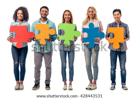 Young people of different nationalities with colorful pieces of puzzle are looking at camera and smiling, isolated on white background - stock photo