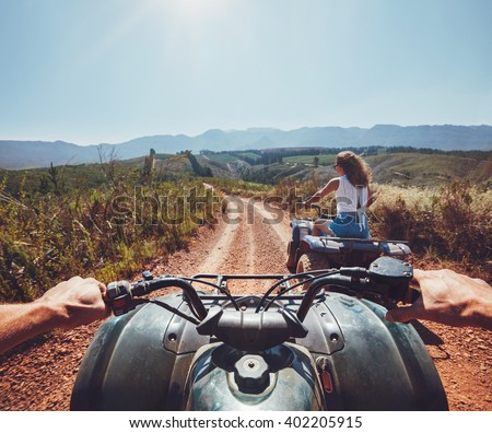Young people on quad bikes on a countryside trail. View from a quad bike with woman driving an ATV in front on a sunny day. - stock photo