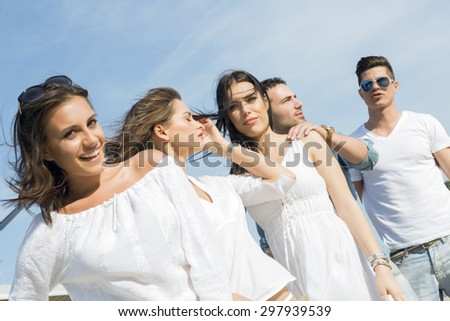 Young people on the beach posing with wind blowing their hair - stock photo