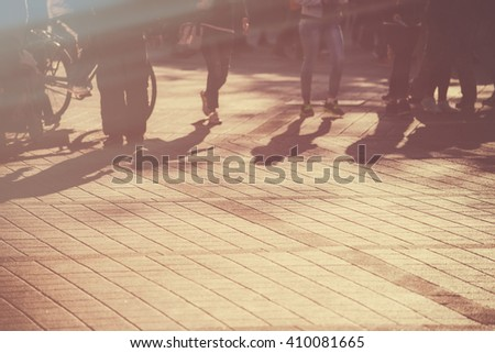 Young people on the street, blur defocussed image of young pedestrians walking in late afternoon, retro toned - stock photo