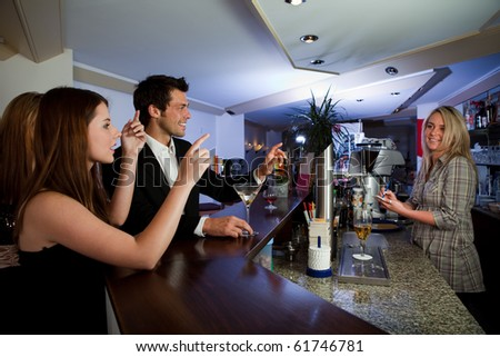 Young people ordering drinks at the bar. Focus on the men - stock photo