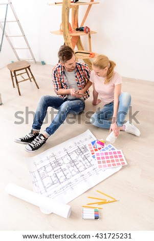 Young people pick up color of paint for repair - stock photo