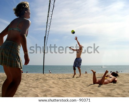 Young people playing volleyball at the beach - stock photo