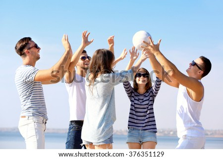 Young people playing with ball on the riverside - stock photo