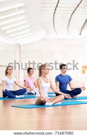 Young people practice yoga in the fitness club - stock photo