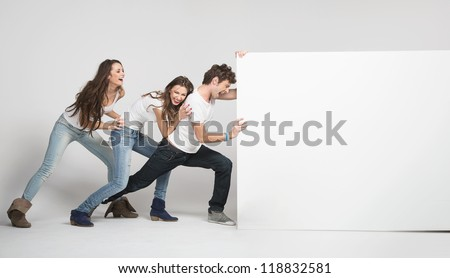 Young people pushing white board - stock photo