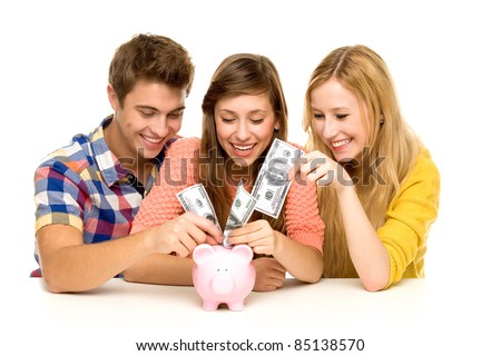 Young people putting money in piggy bank - stock photo