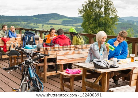 Young people relax mountain holiday summer sport drinking and eating - stock photo