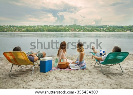 Young people relaxing on the beach enjoying view - stock photo