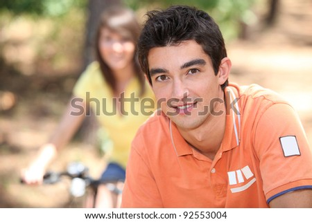 Young people riding bikes in the forest - stock photo