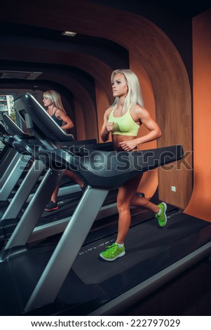 young people running on treadmill in gym  - stock photo